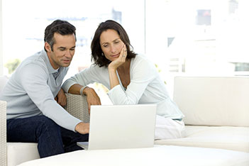 Couple sitting on their couching looking at a business' website